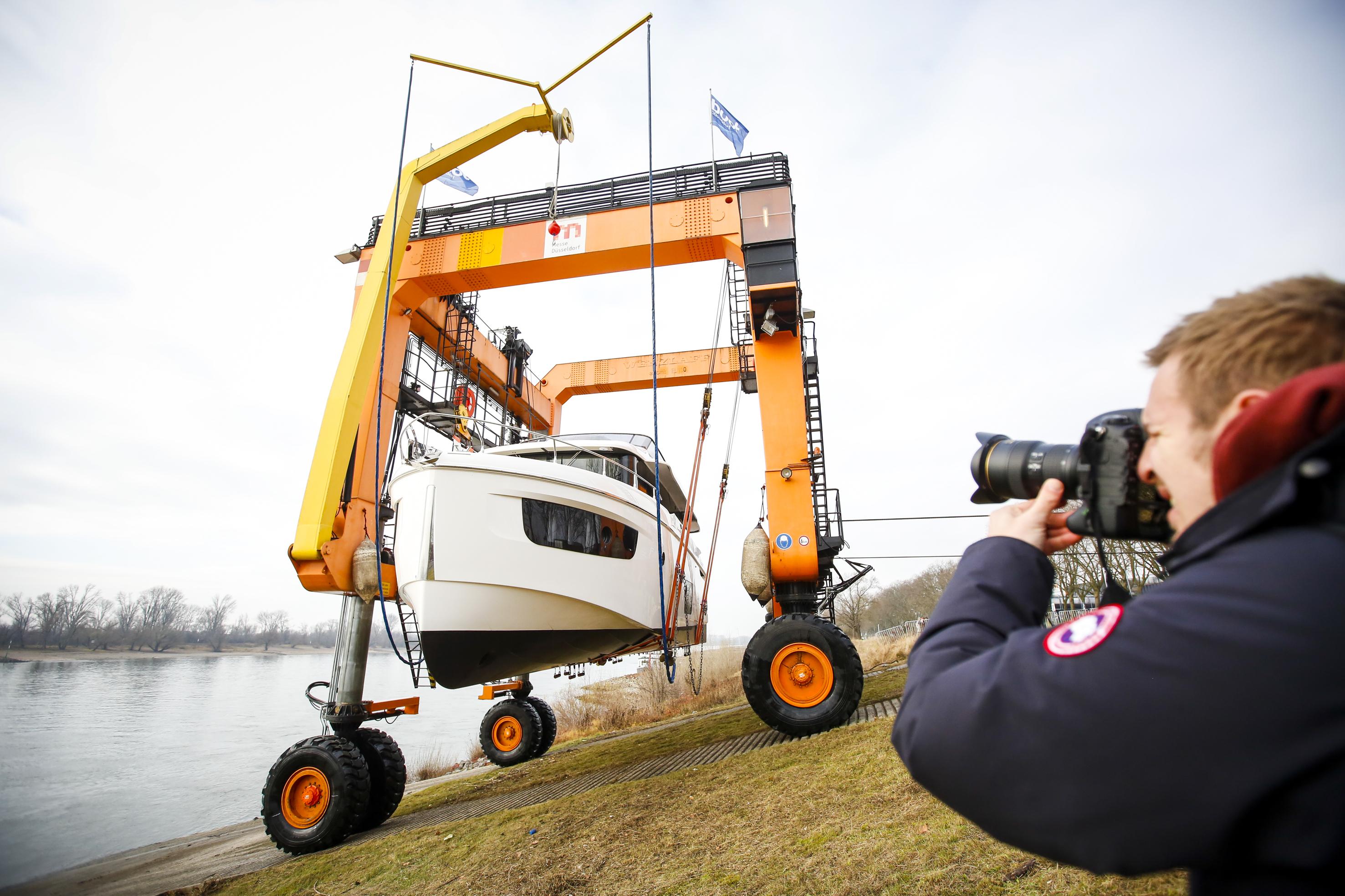 """Von Big Willis starken Armen aus dem Rhein gehoben zu werden, davon träumen die Luxusyachten, die sich ab jetzt auf den Weg zur boot nach Düsseldorf machen. Am 14. Dezember startet mit der Auskranung der Elling E6 aus der niederländischen Neptune Marine Werft in Aalst, der italienischen Navetta 52 und """"Absolute 60 Fly"""" aus der Absolute Werft in Podenza in der Emilia Romagna der Auskranungsreigen zur boot 2017. Schwergewicht """"Big Willi"""", er wiegt 84 Tonnen und kann bis zu 100 Tonnen schwere Schiffe tragen, rollt mühelos in die Fluten des Rheins. Dort hebt er bis zu Beginn der boot am 21. Januar bis zu 29 Luxus-, Motor- und Segelyachten aus dem Wasser auf einen Tieflader, der die Traumschiffe in ihre temporäre Heimat in den Düsseldorfer Messehallen fährt.   Mit kraftvoller Eleganz gleitet die """"Elling E6"""" mit ihrem 900 PS Volvo Penta 6-Zylinder Motor durchs Wasser. Der Transatlantik Kreutzer misst 65 Fuß (20 Meter) und ist 19 Tonnen schwer. Der Preis für das neue Flagschiff der Elling E-Linie liegt bei 1.725.500 Euro. Am Mittwochmorgen lag sie als erstes Boot für die boot Düsseldorf 2017 in Big Willis Armen und wurde zu ihrem Stand B21 in Halle 17 transportiert.   Als Juwel in den Wellen bezeichnet die italienische Absolute Werft ihre Navetta 52. Sie besticht mit Eleganz und Funktionalität, ist mit zwei 435 PS starken Volvo Penta IPS600s Motoren ausgestattet, misst 52 Fuß (15,84 Meter) und wechselt für 1.119.545 Euro den Besitzer. Am Mittwoch um 12:00 Uhr wurde die Luxusyacht aus der italienischen Absolute Werft von Big Willi an Land gehoben.   Dritte im Bunde am ersten Auskranungstag der boot 2017 war um 14:00 Uhr die """"Absolute 60 FLY"""". Sie ist ein luxuriöses 60-Fuß-Boot, glänzt mit drei Sonnendesks, konzipiert für die Freizeit, den Cocktail-Empfang oder Banketts. Die """"Absolute 60 Fly"""" ist 18,4 Meter lang, motorisiert mit 2 x 725 CV Volvo IPS, fährt eine maximale Höchstgeschwindigkeit von 32 Knoten (64,82 kmh) und eine Reisegeschwindigkeit von 25 Knoten (46,3 kmh), ih"""