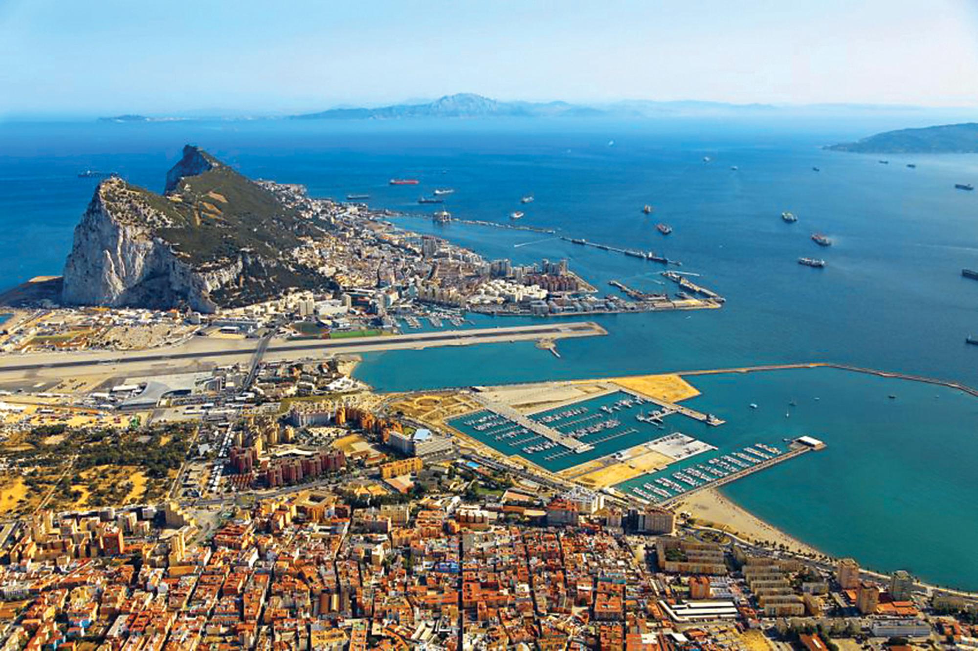 Скеля Гібралтар. Під нею – злітна смуга, через яку проходить автомобільна дорога. На задньому плані – Марокко, Африка